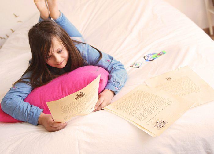 Une petite fille plongée dans la lecture de l'aventure personnalisée, conçue spécialement pour elle.