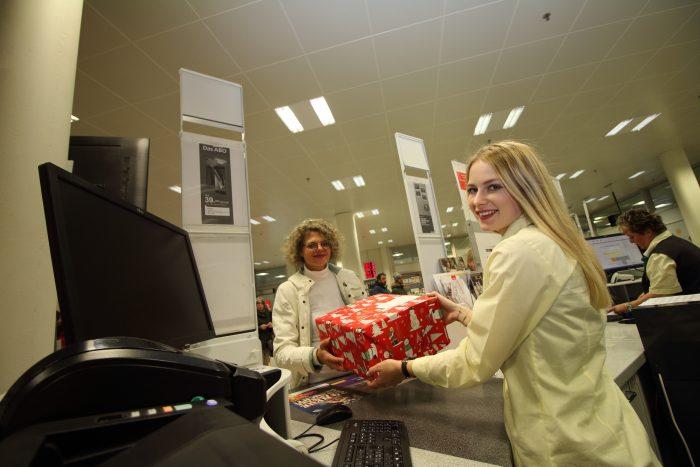 Schön verpackt übergibt Barbara Schluchter-Donski das Päckli am Postschalter in der Thuner Hauptpost der Postmitarbeiterin. Danach wird es zusammen mit anderen Paketen in einen Lieferwagen eingeladen. Diese Arbeit erledigen die Postmitarbeiter von Hand. Nach rund einer Stunde trifft unser Weihnachtspäckli in der Distributionsbasis Thun-Rosenau ein. Die Pakete werden dort so schnell wie möglich sortiert und gemeinsam mit Briefen und anderen Sendungen in einen LKW verladen. Einmal verladen, geht die Reise für unser Päckli Richtung Paketzentrum Härkingen weiter. Nach ungefähr zwei Stunden ist es soweit, das Weihnachtspäckli rutscht in Härkingen in den Verarbeitungsprozess.