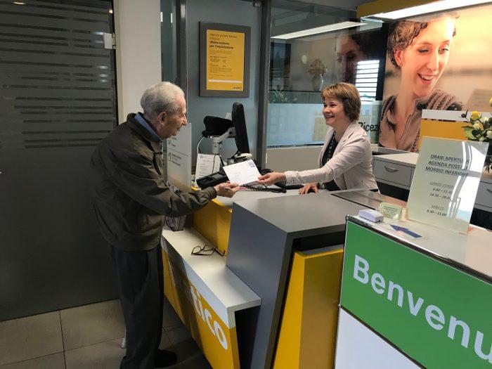 Roberto Ferrari reicht der Mitarbeiterin der Filiale seinen Brief. / Bild: Nathalie Dérobert