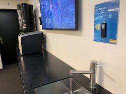 """Nicht mehr alle Tassen im Schrank? Mitarbeitende lösen beim """"Service on demand"""" per Fingerdruck auf Smart Buttons den Support bei Störungen der Kaffeemaschine oder Mikrowelle aus."""