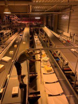 Il responsabile team dei tecnici d'esercizio, Daniel Büttler, raddrizza una barra spostata affinché i pacchi possano scivolare in modo preciso attraverso l'impianto raggiungendo il corridoio a cui sono destinati.