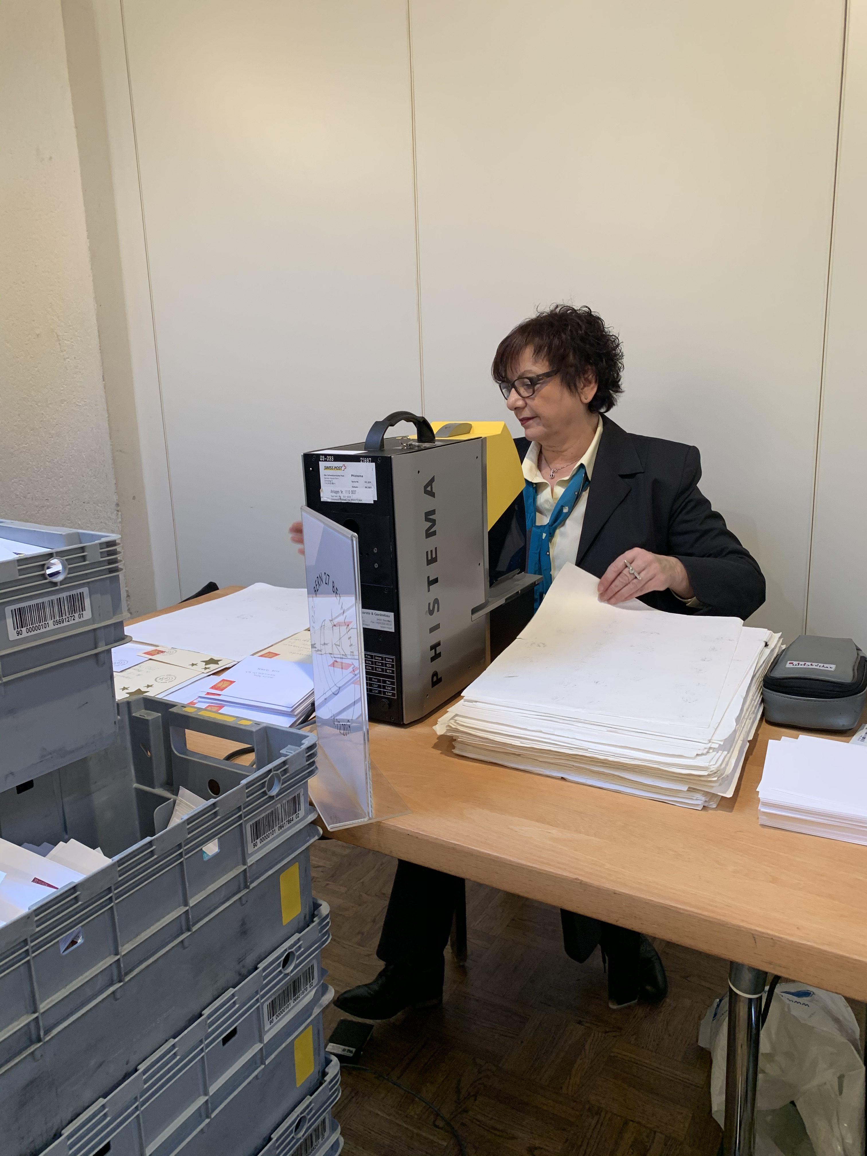 Valéria Strässle stempelt jeden Brief mit einer Frankaturmaschine von Hand