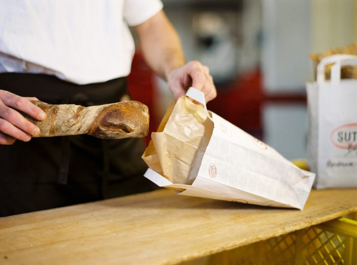 Di prima mattina la panetteria locale confeziona con cura il pane per ogni ordinazione… …in modo che più tardi il postino possa consegnarlo a domicilio insieme alla posta. I Immagini: La Posta Svizzera